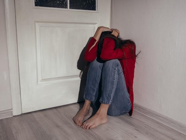 Przygnębiona dziewczyna w czerwonej koszuli pod ścianą