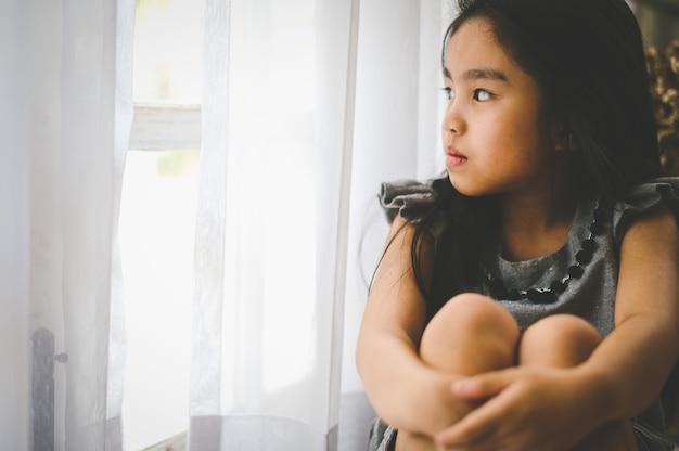 Przygnębiona dziewczynka w pobliżu okna w domu, zbliżenie