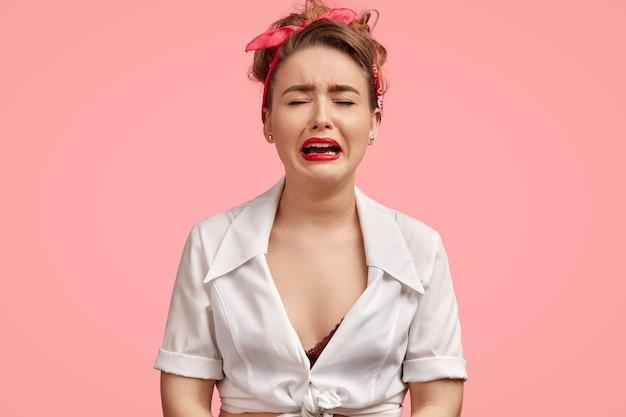 Przygnębiona europejka w przygnębieniu, rozpaczliwie płacze, ma czerwone usta, zamyka oczy, ma smutek, nosi białą bluzkę i opaskę na głowie.