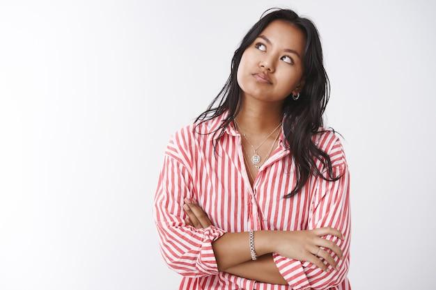 Przygnębiona i pod presją młoda niecierpliwa kobieta wpatrująca się w lewy górny róg, sprawdzająca czas skrzyżowane ramiona na klatce piersiowej i uśmiechająca się, niezadowolona z wolnej kolejki, pozująca na białym tle
