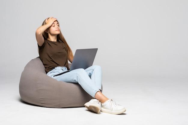 Przygnębiona i sfrustrowana kobieta pracuje z komputerem laptop zdesperowana w pracy na białym tle. depresja
