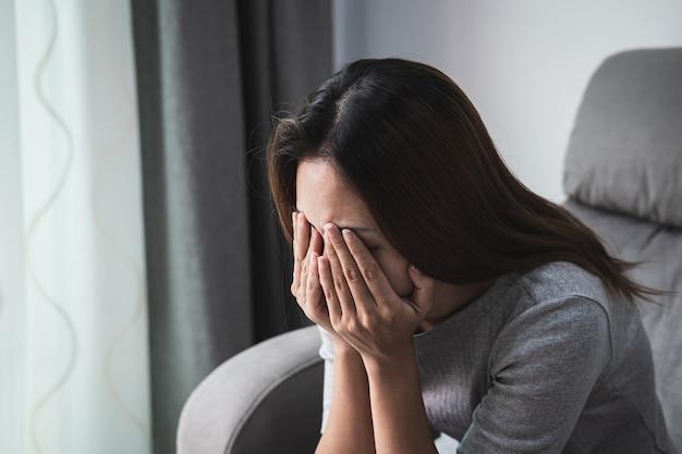 Przygnębiona i smutna kobieta płacze sama w domu