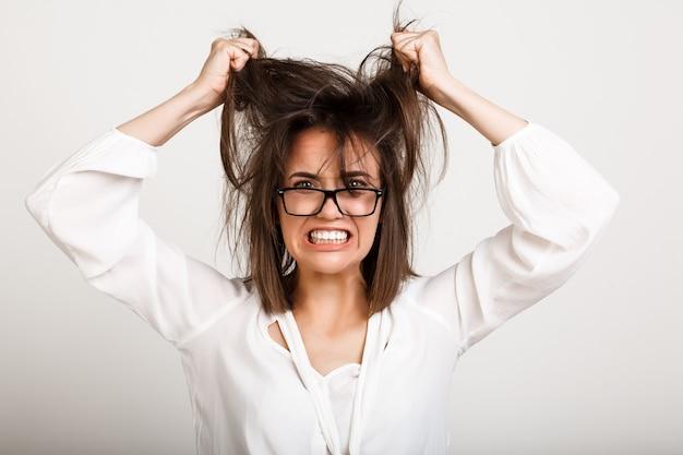 Przygnębiona kobieta ma emocjonalne wypalenie zawodowe, ciągnie włosy