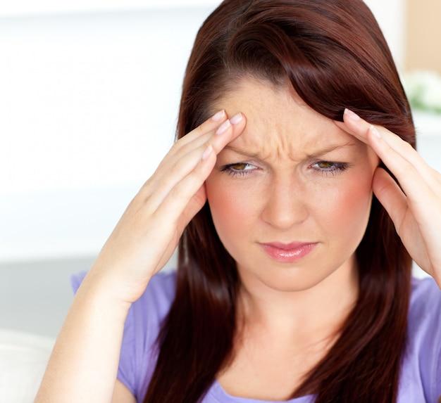 Przygnębiona kobieta o ból głowy siedząc w salonie
