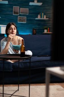 Przygnębiona kobieta ogląda dramat w telewizji, płacze z emocjonalną ekspresją