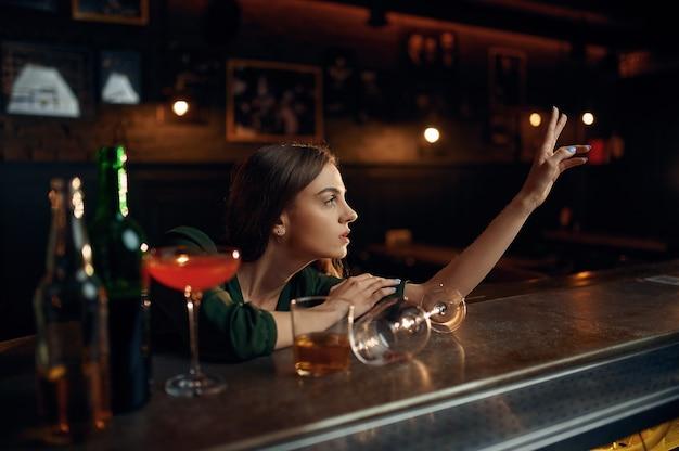 Przygnębiona kobieta pije alkohol przy kasie w barze