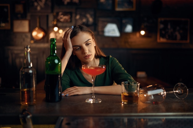 Przygnębiona kobieta pije inny alkohol przy kasie w barze
