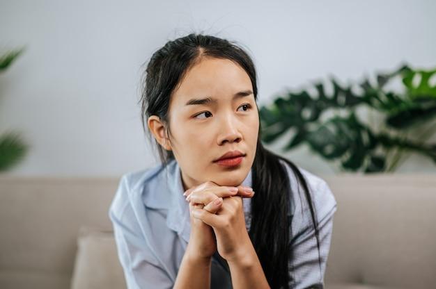 Przygnębiona kobieta siedzi na kanapie w domu, myśli o ważnych rzeczach lub czuje się nieszczęśliwa z powodu problemów w życiu osobistym, kopiuje przestrzeń