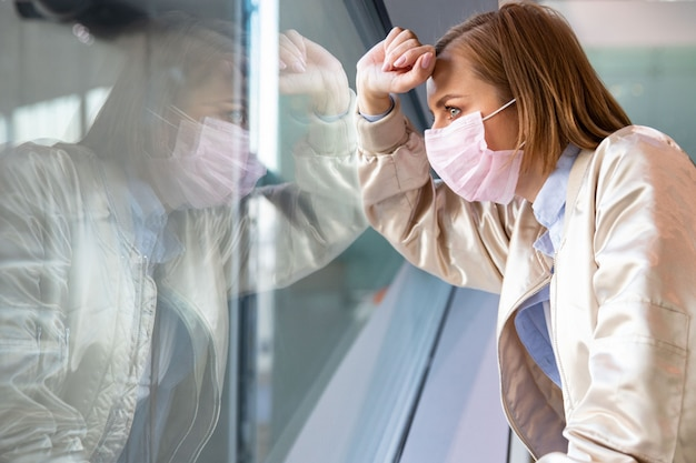 Przygnębiona kobieta ubrana w maskę medyczną, patrząc przez okno na puste miasto