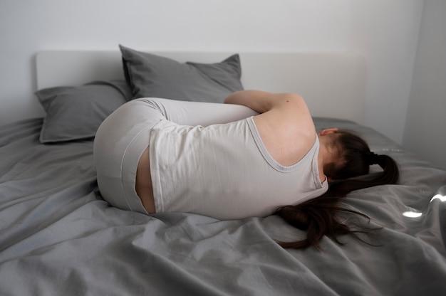 Przygnębiona kobieta w łóżku pełny strzał