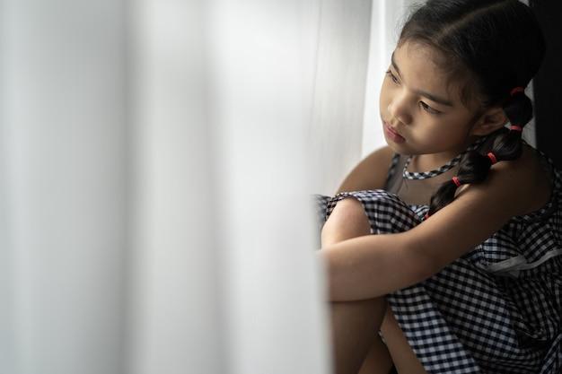 Przygnębiona mała dziewczynka blisko okno w domu, zbliżenie