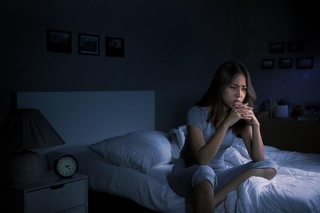 Przygnębiona młoda azjatka siedząca w łóżku nie może zasnąć z powodu bezsenności