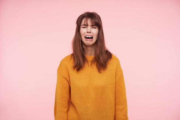 Przygnębiona młoda brunetka marszczy brwi z zamkniętymi oczami i smutno płacze z otwartymi ustami, ubrana w musztardowy wełniany sweter, pozując na różowej ścianie