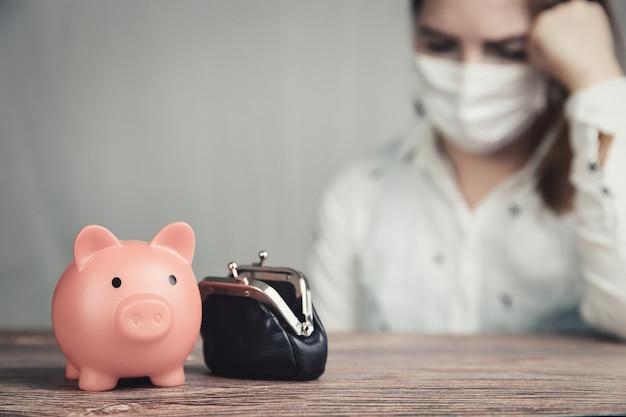 Przygnębiona młoda kobieta biznesu z różową skarbonką dla oszczędności i noszącą maskę ochronną dla covid-19