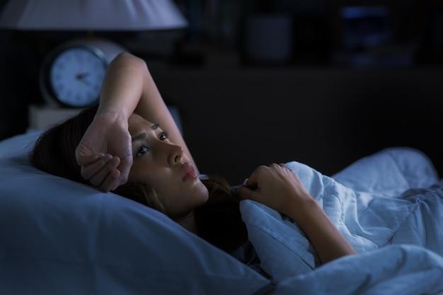 Przygnębiona młoda kobieta leżąca w łóżku nie może zasnąć z powodu bezsenności