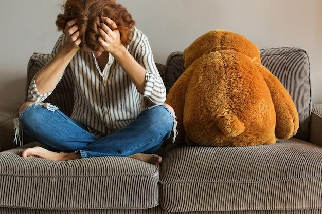 Przygnębiona młoda kobieta na kanapie stresuje lęk samotność