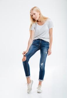 Przygnębiona młoda kobieta pokazująca podarte spodnie na białej ścianie