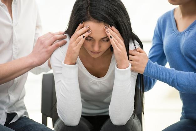 Przygnębiona młoda kobieta siedzi na krześle.