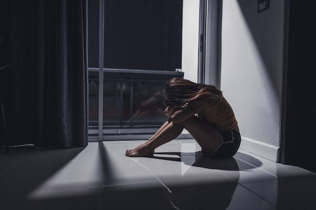 Przygnębiona młoda kobieta siedzi samotnie na podłodze w salonie.