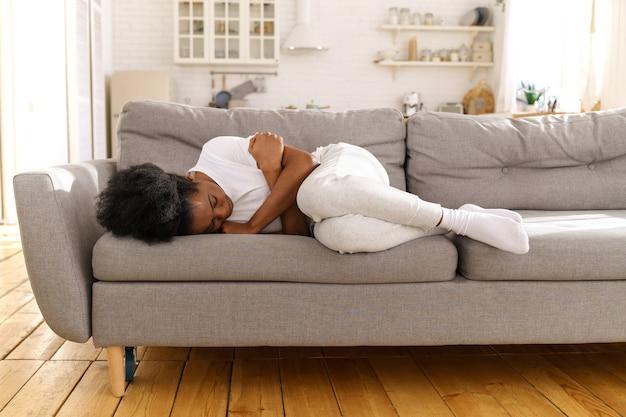 Przygnębiona nieszczęśliwa czarna kobieta leżąca na kanapie w domu, płacząca, cierpiąca na rozwód lub zerwanie.