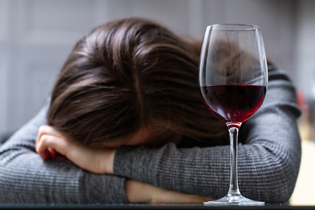 Przygnębiona, rozwiedziona płacząca kobieta siedząca samotnie w kuchni w domu i pijąca kieliszek czerwonego wina z powodu problemów w pracy i problemów w związkach. problemy społeczne i życiowe