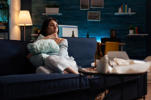 Przygnębiona, sfrustrowana, zestresowana, straumatyzowana kobieta siedząca samotnie trzymająca poduszkę, wrażliwa emocjonalnie, samotna zdesperowana, przestraszona cierpiąca z powodu rozstania mająca niepokój, problemy ze zdrowiem psychicznym
