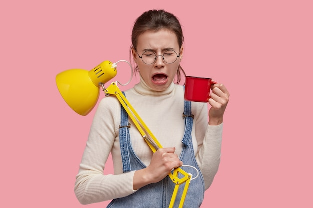 Przygnębiona smutna kobieta otwiera usta, rozpaczliwie płacze, trzyma czerwoną filiżankę herbaty, lampka na biurku