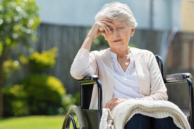 Przygnębiona stara kobieta na wózku inwalidzkim