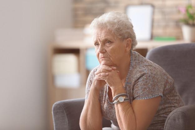Przygnębiona starsza kobieta w domu