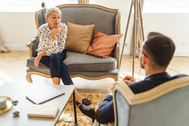 Przygnębiona starsza pani z podpartym podbródkiem, siedząca na sofie w swoim gabinecie psychoanalityka