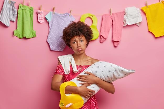 Przygnębiona zmęczona matka dba o niemowlę, ma nieprzespaną noc i dużo prac domowych, potrzebuje drzemki, stara się uspokoić płaczące dziecko, wyczerpana opieką nad dzieckiem, zajęta wykonywaniem prac domowych, pierze dziecięce ubrania