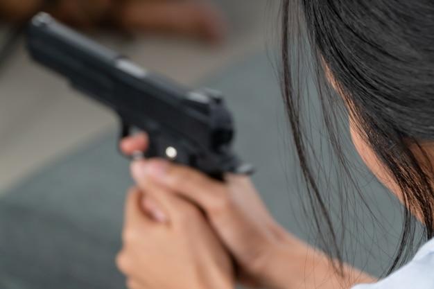 Przygnębione kobiety w średnim wieku trzymające broń w salonie z powodu stresu w życiu i niezdolne do znalezienia rozwiązania i braku doradcy.