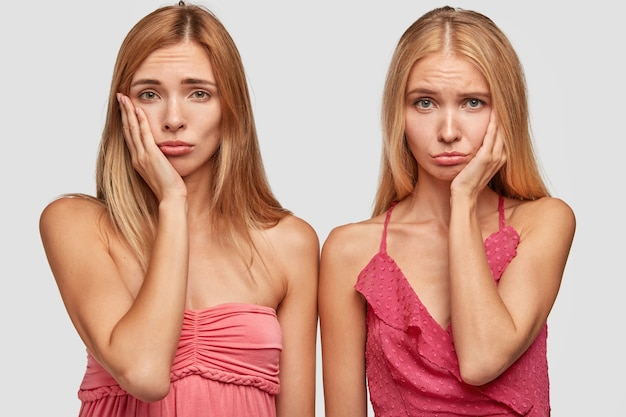Przygnębione smutne blond siostry lub najlepsi towarzysze marszczą brwi i trzymają ręce na policzkach, będąc w złym nastroju