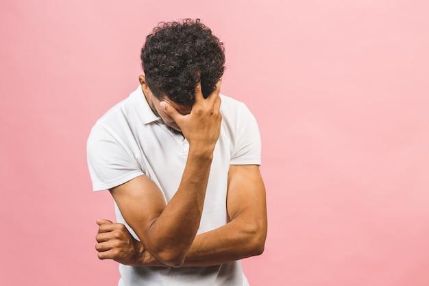 Przygnębiony amerykanina afrykańskiego pochodzenia mężczyzna z rękami na twarzy. nieszczęśliwy facet przejmował się błędami. rozczarowanie, frustracja, porażka. różowe tło z wolnego miejsca.