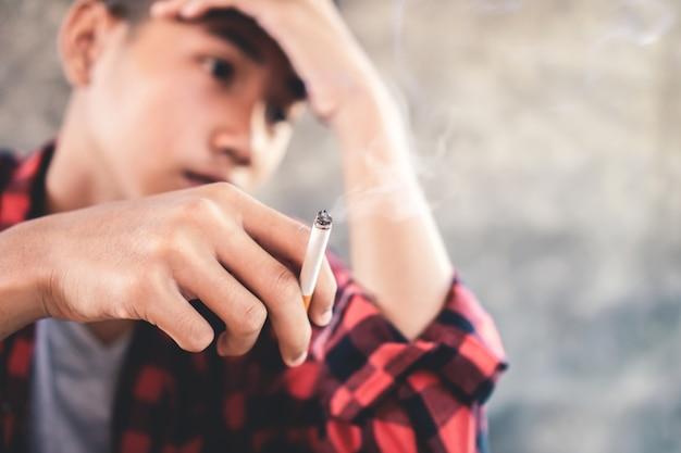 Przygnębiony azjatycki nastoletni chłopak pali papierosa