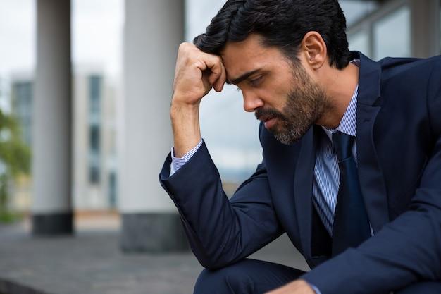 Przygnębiony biznesmen siedział z ręką na czole w pomieszczeniach biurowych
