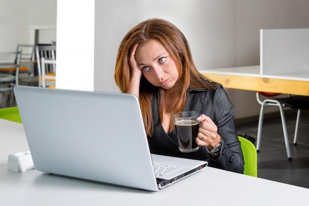 Przygnębiony bizneswomanu obsiadanie przy komputerem