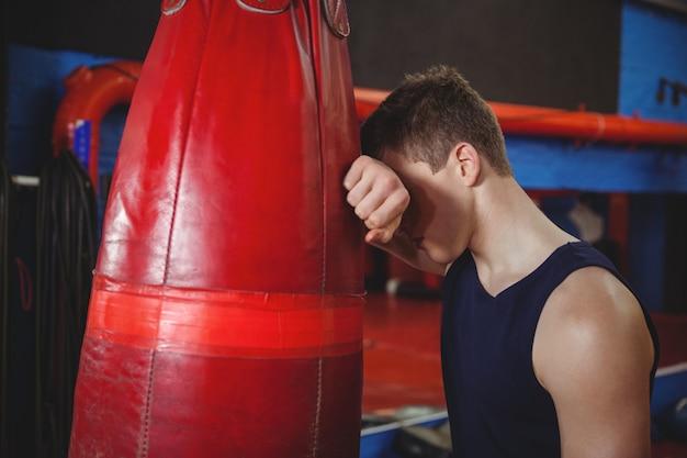 Przygnębiony bokser oparty o worek treningowy