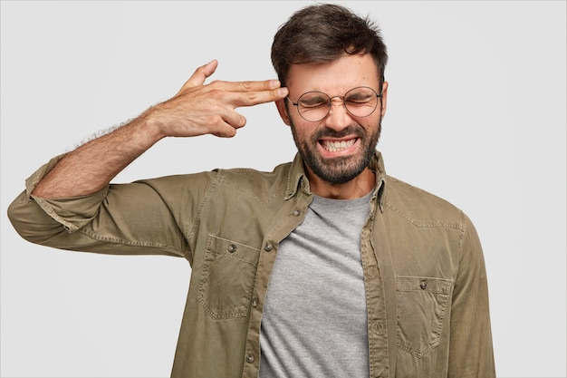 Przygnębiony, brodaty samiec zaciska zęby, strzela ręką w skroń, udaje, że zabija się wszystkim, pozuje przy białej ścianie. atrakcyjny mężczyzna stara się unikać wszelkich problemów