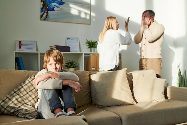 Przygnębiony chłopiec cierpi z powodu konfliktu rodziców