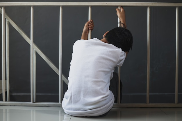 Przygnębiony chłopiec siedzi sam w domu
