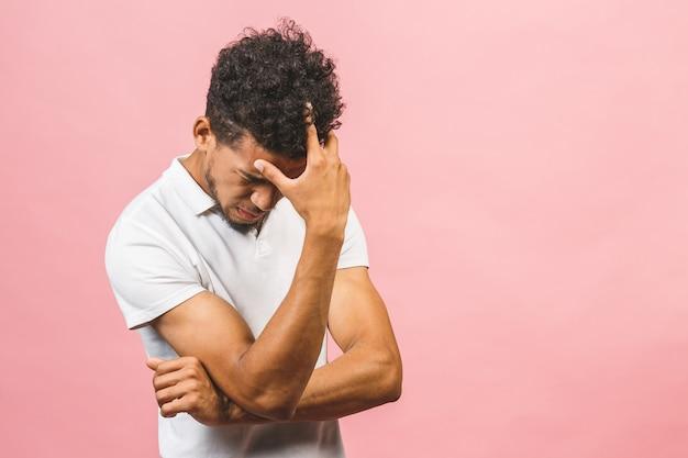 Przygnębiony człowiek afroamerykanin z rękami na twarzy. nieszczęśliwy facet przejmował się błędami. rozczarowanie, frustracja, porażka. różowe tło.