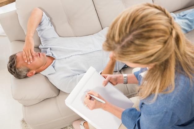 Przygnębiony człowiek leżący na kanapie i mówić do terapeuty
