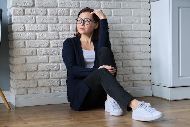 Przygnębiony dojrzały kobiety obsiadanie na podłoga w domu