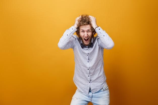 Przygnębiony histeryczny młody człowiek krzyczy na żółtym backg