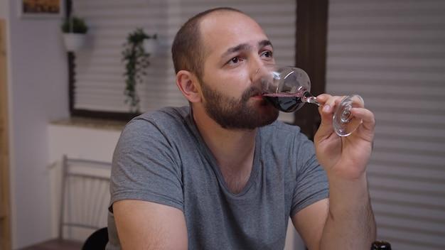 Przygnębiony mężczyzna pije samotnie w kuchni. nieszczęśliwa osoba cierpiąca na migrenę, depresję, choroby i stany lękowe, wycieńczona z objawami zawrotów głowy, mająca problemy z alkoholizmem.