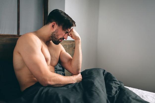 Przygnębiony mężczyzna siedzi na łóżku w pustym pokoju, jest to poważne zaburzenie depresyjne