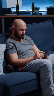 Przygnębiony mężczyzna słucha muzyki za pomocą słuchawek siedzących samotnie