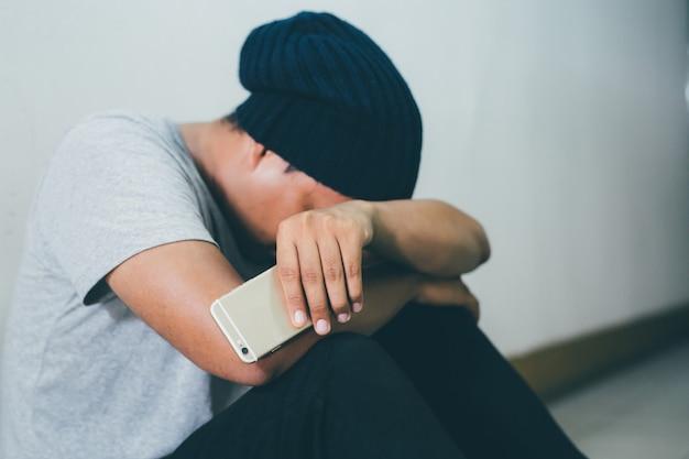 Przygnębiony mężczyzna trzyma smartfon