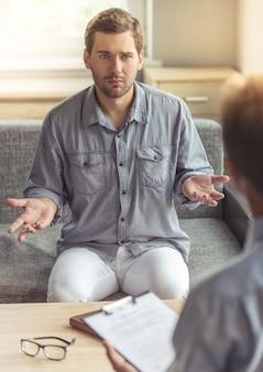 Przygnębiony mężczyzna w zwykłych ubraniach opowiada swoje problemy.